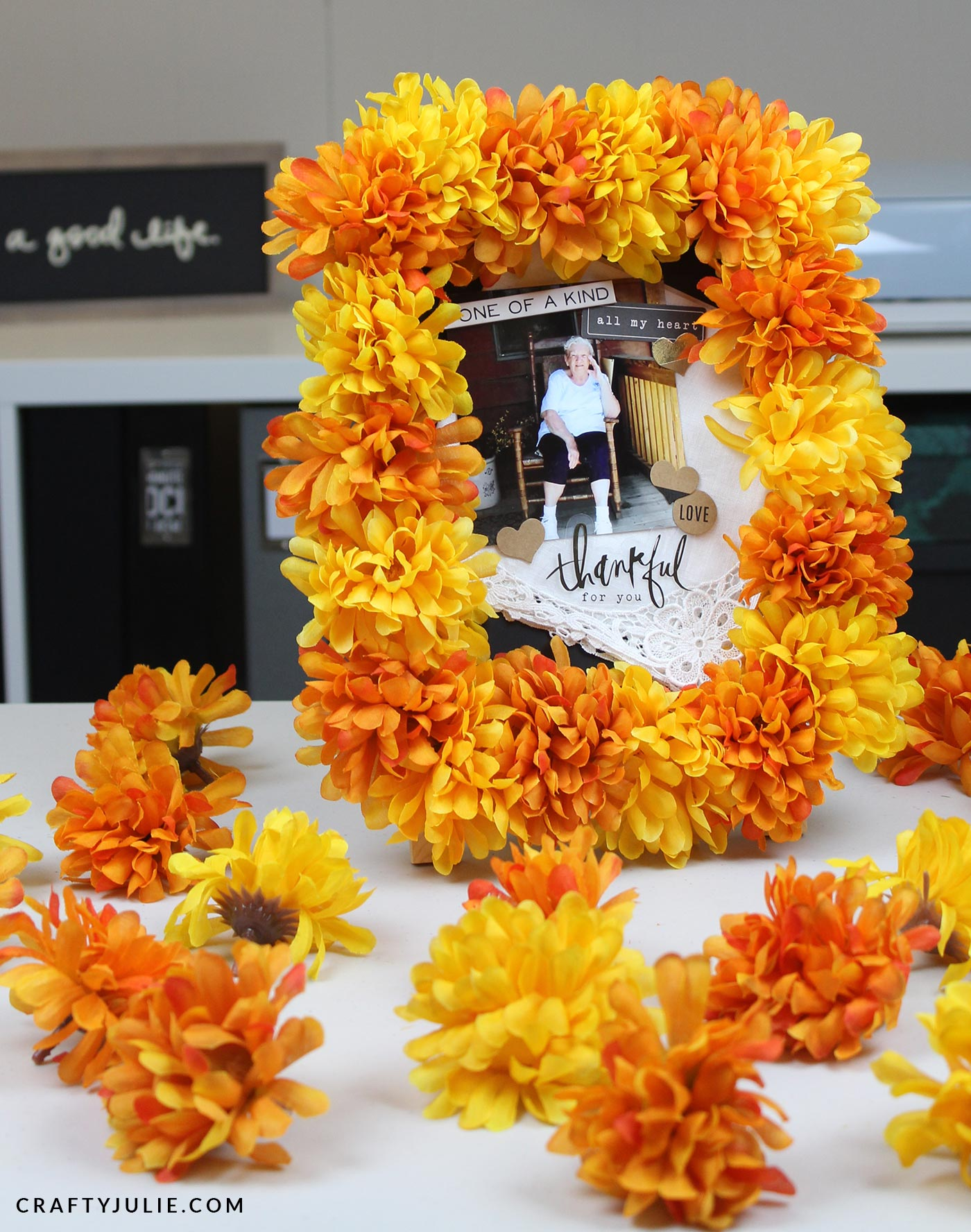 Picture frame surrounded by orange and yellow flowers