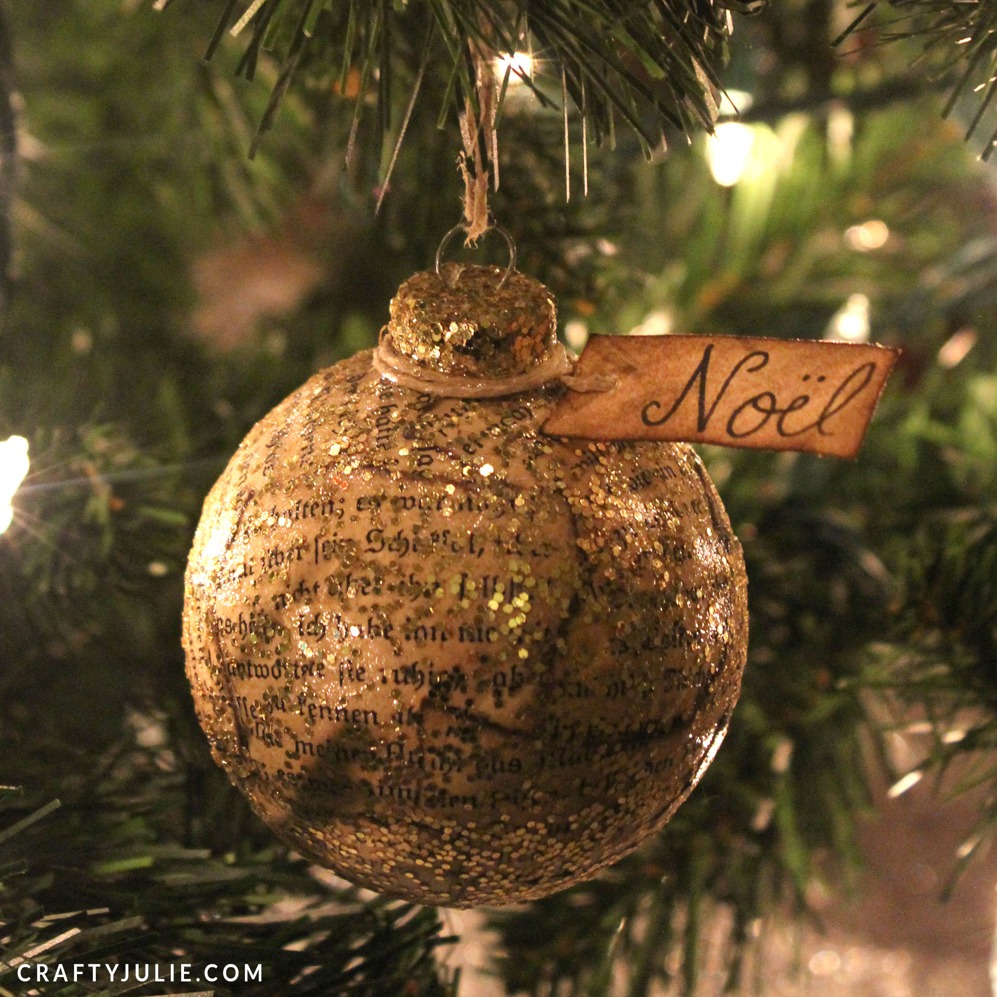 gold glittered book page ornament with noel tag hanging on tree