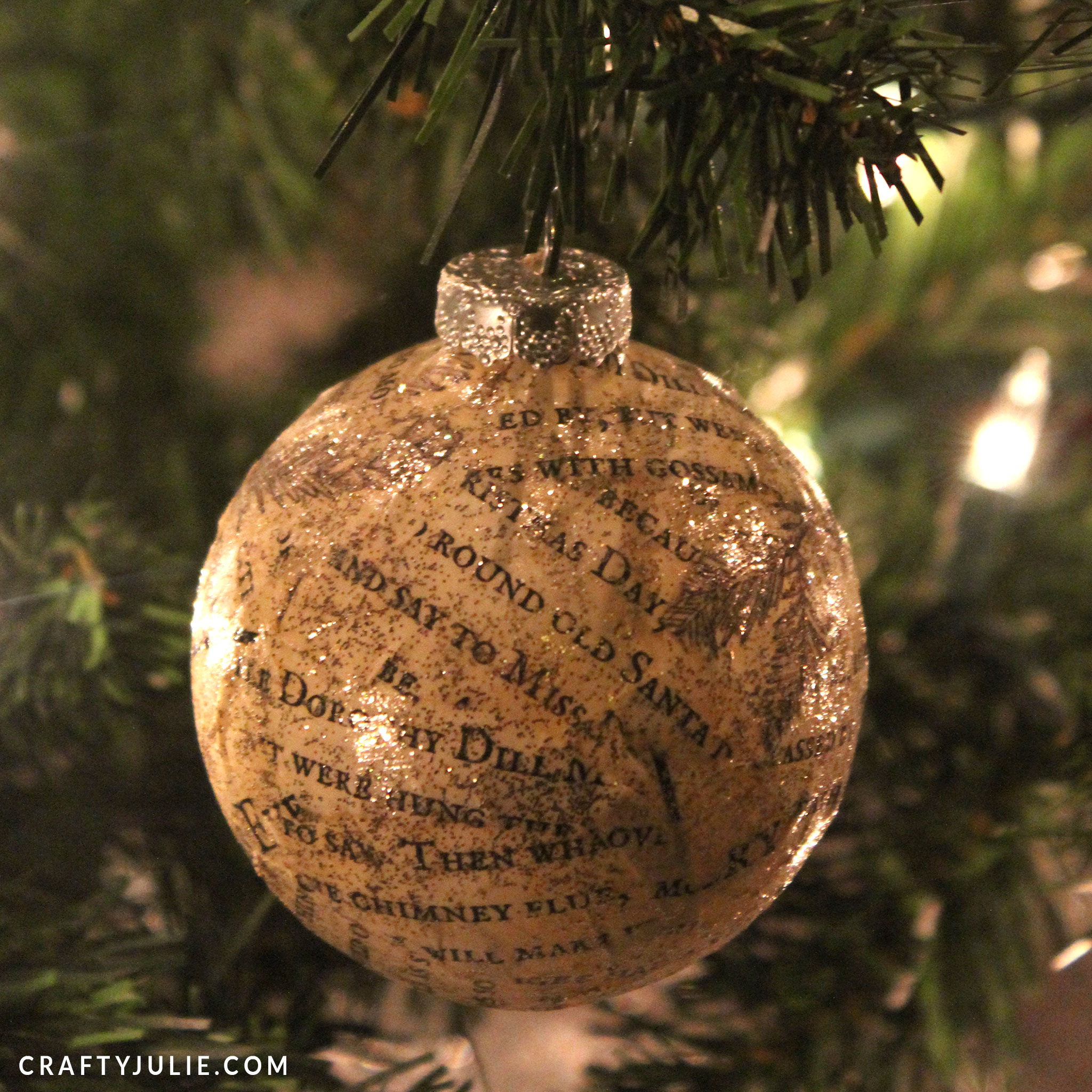 light colored book page ornament hanging on tree