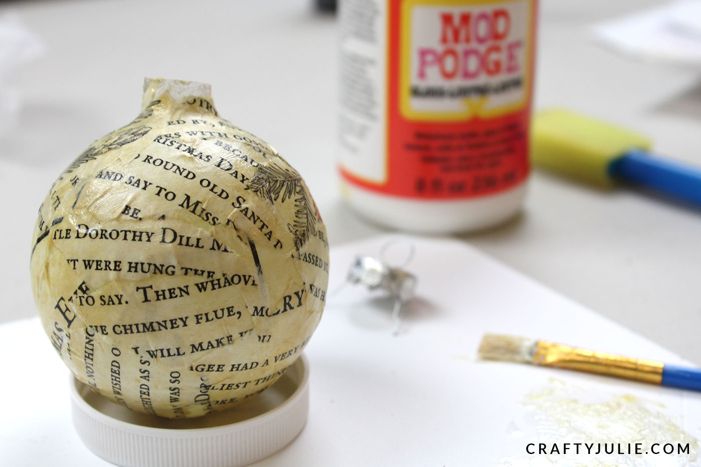torn book pages applied to glass bulb ornament using mod podge
