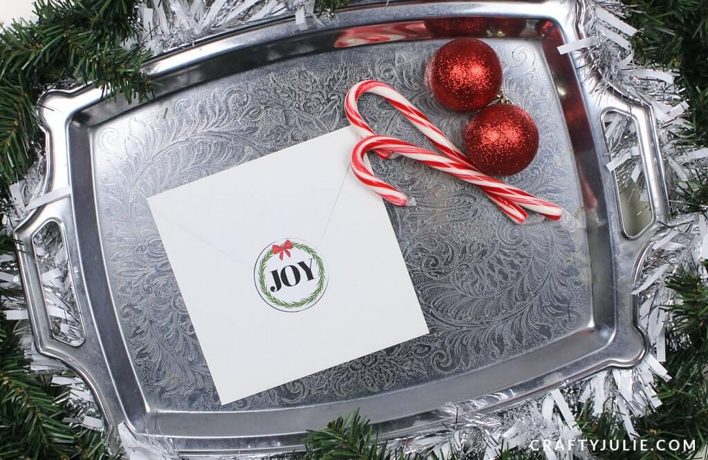 Envelope with Holiday Sticker Seal that says JOY sitting on a metal tray