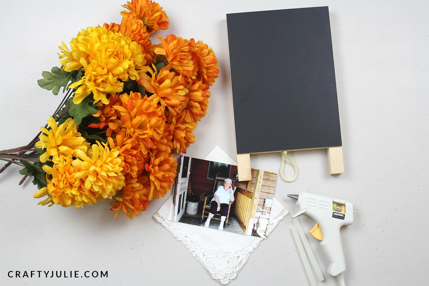 mini chalkboard easel, orange and yellow fake flowers, glue gun, and photo used to make easy DIY flower picture frame